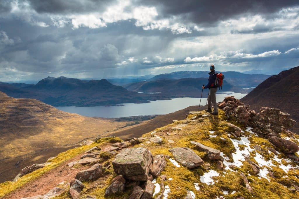 The silhouette of a hiker in a mountain wilderness scene in Scotland, UK.